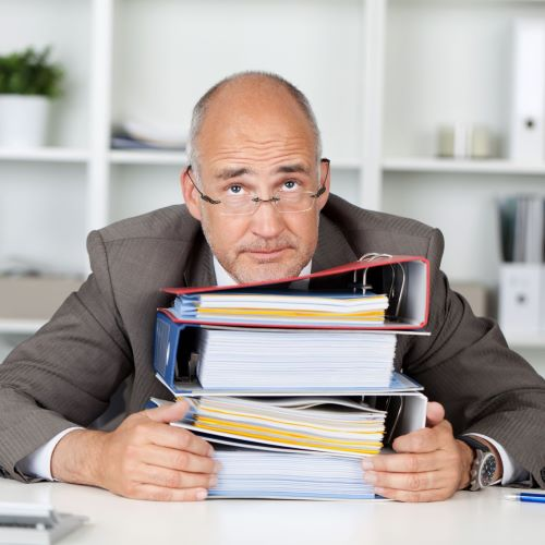 confused man with stack of documents